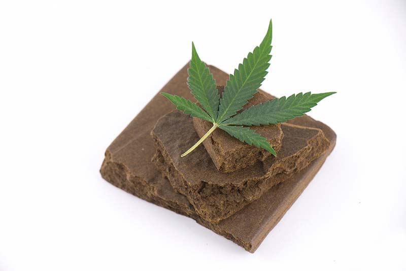 Small block of hash with cannabis leaf